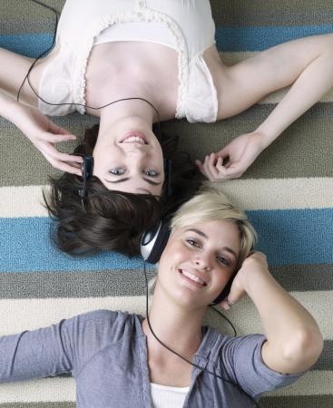 leis: Due giovani donne che ascolta le cuffie Archivio Fotografico