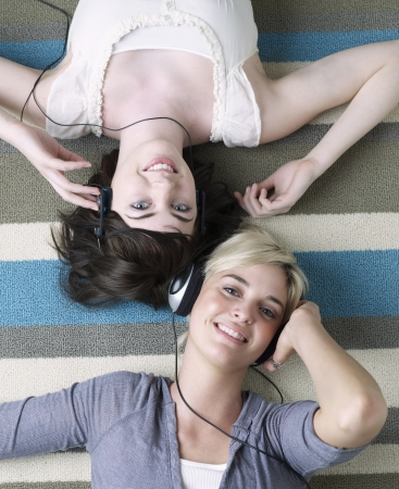 leis: Two Young Women Listening to Headphones Stock Photo