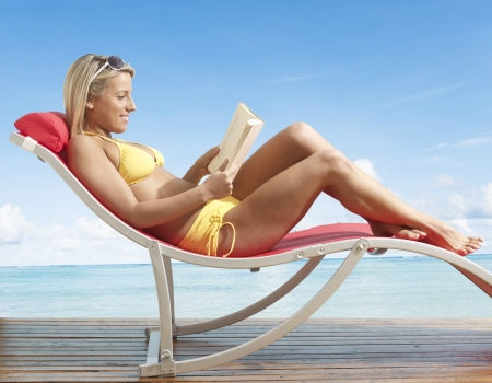 Young Woman Reading Book on Lounge Chair photo