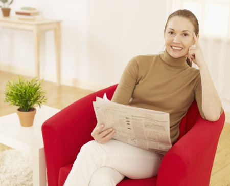 Mid-Adult Woman Reading Newspaper in Living Room photo