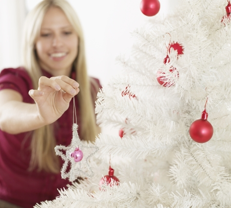 decorating christmas tree: Mid-Adult Woman Decorating Christmas Tree