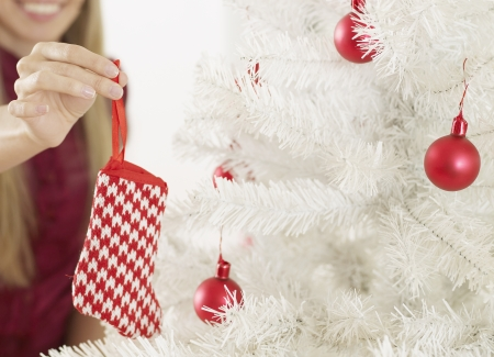 decorating christmas tree: Close-Up of Woman Decorating Christmas Tree Stock Photo