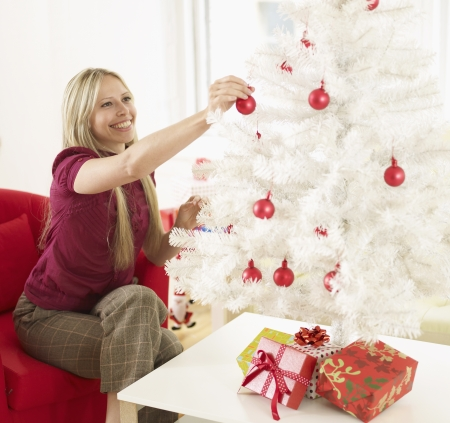 Mid-Adult Woman Decorating Christmas Tree photo