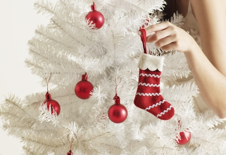 fake christmas tree: Mid-Adult Woman Decorating Christmas Tree