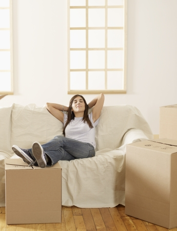 Mid-Adult Woman Resting by Cardboard Boxes photo