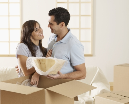 Mid-Adult Couple Unpacking Cardboard Boxes photo