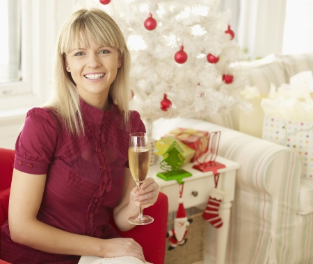 Mid-Adult Woman Celebrating Christmas with Champagne photo