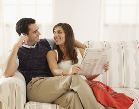 Mid-Adult Couple Reading and Using Mobile Phone on Sofa photo