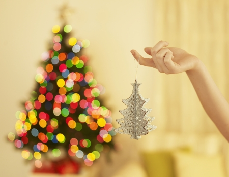 Womans Hand Holding Christmas Decoration photo