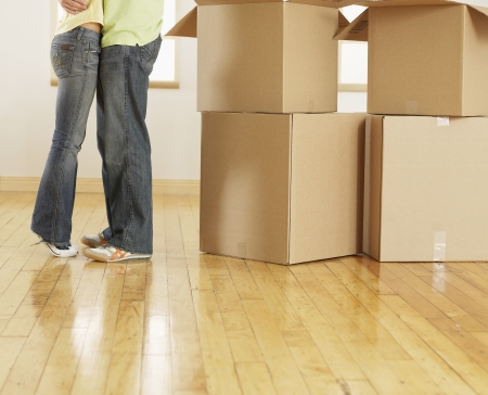 Low Section of Couple Hugging by Cardboard Boxes photo