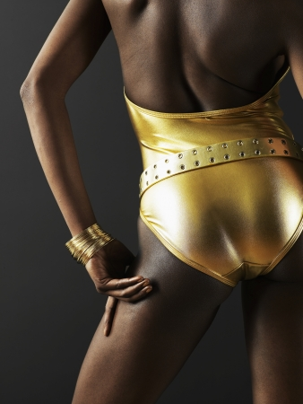 swimming costume: Rear View of Woman Wearing Golden Swimming Costume Stock Photo