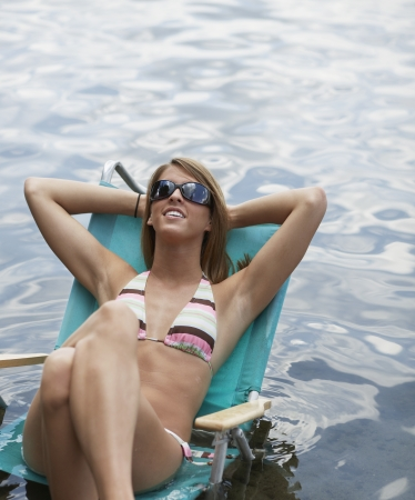 Teenage Girl Relaxing on Lounge Chair in Water photo