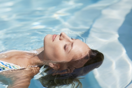 Mid-Adult Woman Floating in Swimming Pool photo