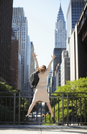 Businesswoman with Backpack Jumping photo