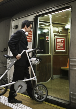 Businessman with Bicycle Boarding Subway Train photo