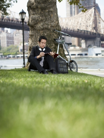 Businessman Making Notes Under Tree photo