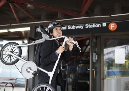 Businessman Carrying Bicycle to Subway Station photo