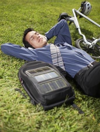 Young Businessman with Bicycle Lying on Grass photo