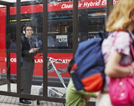 Businessman Listening to MP3 Player at Bus Stop photo