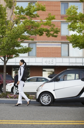 Mid-Adult Woman Walking Near Smart Car photo