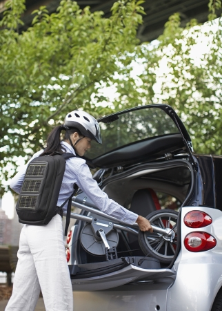 Mid-Adult Woman Putting Bicycle into Car Trunk photo