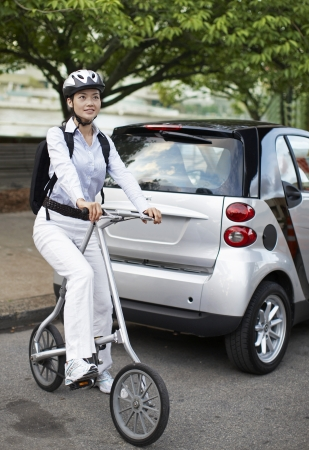 Mid-Adult Woman on Bicycle Beside Smart Car photo