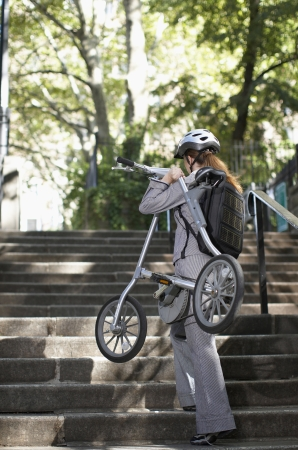 Businesswoman Carrying Bike on Steps photo