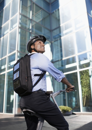 Businessman with Solar Panelled Backpack on Folding Bike photo