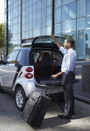 Businessman Unloading Smart Car photo