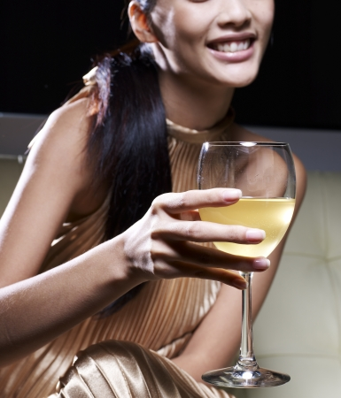 Close-Up of Woman in Evening Dress Drinking White Wine photo