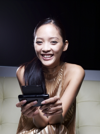 cocktaildress: Mid-Adult Woman in Cocktail Dress Using Cell Phone