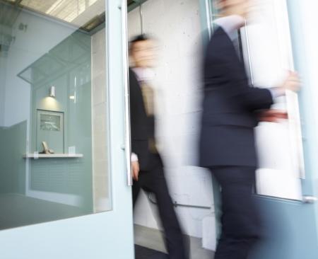 Businesswoman and Businessman Walking Through Door photo