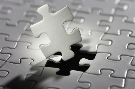 Close up of white jigsaw puzzle piece.   photo