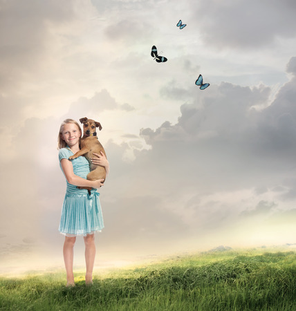 Young Blonde Girl with her Dog on a Magical Mountain photo