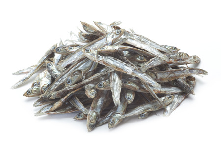 small dried sardines on the white board photo