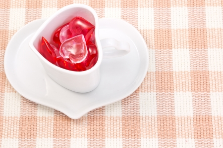 This is a picture of a red and pink hearts and heart shaped cup on the table. photo