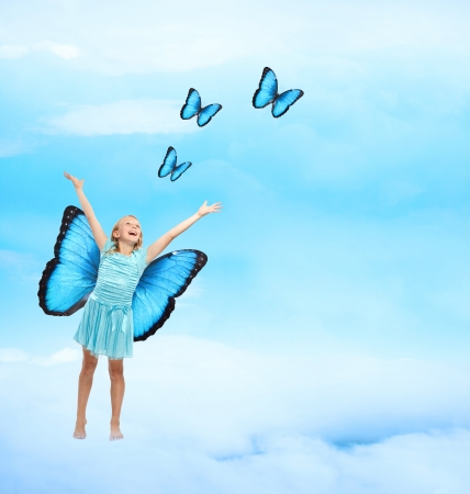 Happy Young Girl in Blue Dress with Arms in the Air Releasing Butterflies  photo