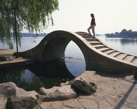 Women Crossing the Bridge Over the Daimei Telecom Engineering Lake photo