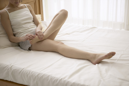qua: Young woman massaging foot on bed Stock Photo