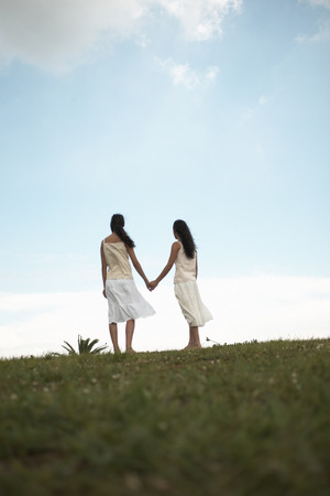 peo: Sisters standing in field holding hands Stock Photo