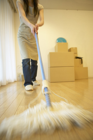 Woman mopping her new house, with boxes in the background. photo