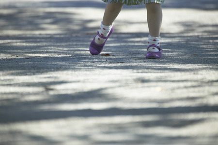 low section view: Low section view of little girl walking on footpath