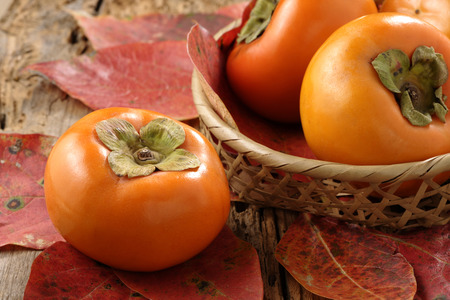 Persimmon fruits and dried leaves Stock Photo