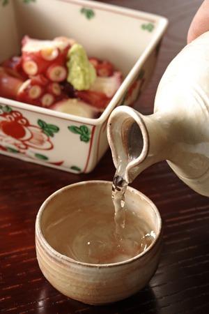 sake: Sake pouring into sake cup Stock Photo