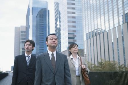 mannen en vrouwen: 3 Japanese business men & women walking Stockfoto