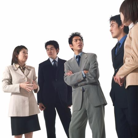 fold ones arms: 5 Japanese business men & women conversing Stock Photo