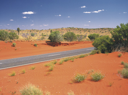 Red sand dunes and a road photo