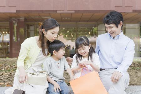 ni�os de compras: La familia japonesa con bolsas de la compra