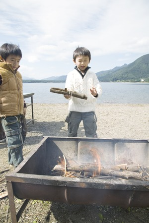 kindling: Asian boys kindling fire