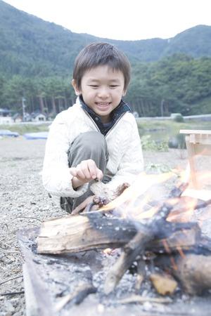 kindling: Asian boy kindling fire